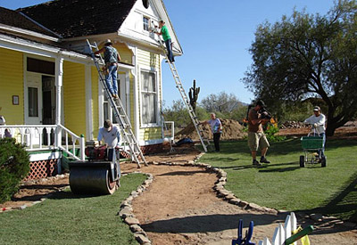 six men working on the front sod lawn of a home