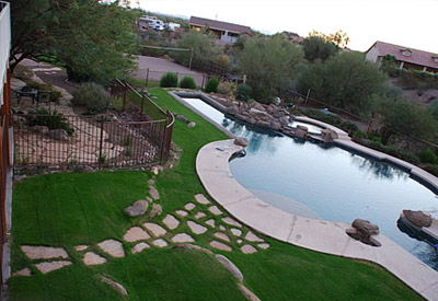 a backyard with a lush green sod lawn, stepping stones and a beautiful pool